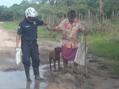Policía bajó de su moto y ayudó a una anciana a cruzar el barro