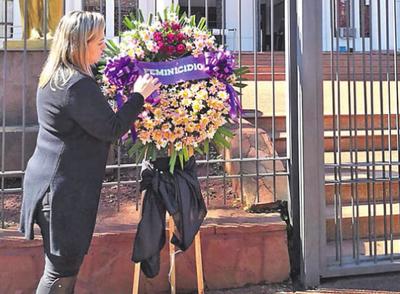 Mujer pide justicia con  una corona de flores