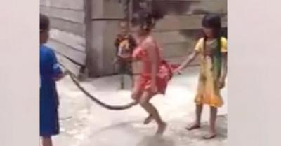 Niños juegan a saltar la cuerda con mbói muerto
