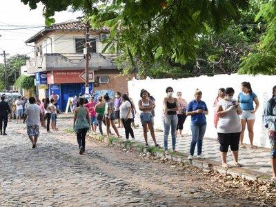 Larga fila de personas para retirar kits de alimentos del MEC