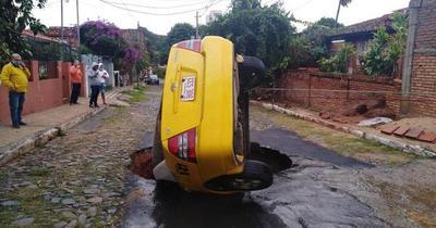 Taxi casi fue tragado por un enorme bache en barrio San Vicente