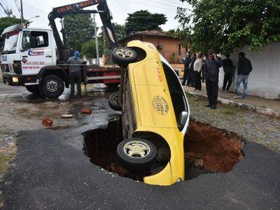 Susto en la calle: Taxi cae a un profundo bache